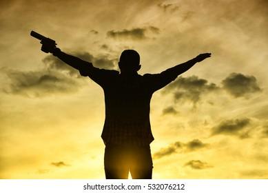 silhouette rear of man standing hand hold holding gun revolvers on sunset,sunrise