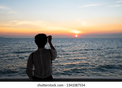 Silhouette rear view of young woman standing near the sea and sky Twilight background for amazing landscape Happy freedom for success and bliss concept.