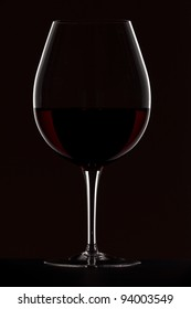 Silhouette of red wine glass isolated on black
