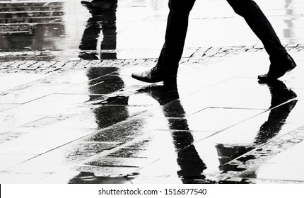 Silhouette and reflection of a man in elegant shoes walking wet city street on s rainy day, legs in black and white