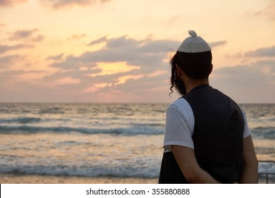 Silhouette of a religious Jewish man contemplating and thinking by the ocean Tel Aviv Israel