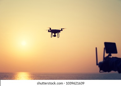 silhouette of remote control a flying drone which taking photo over sunrise sea