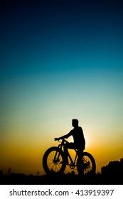 Silhouette of Retro bicycle in summer grass field at sun set