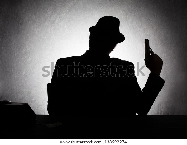 silhouette of retro style gangster holding his gun on grunge background