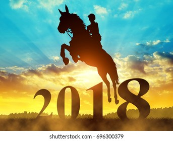 Silhouette the rider on the horse jumping into the New Year 2018 at sunset.
