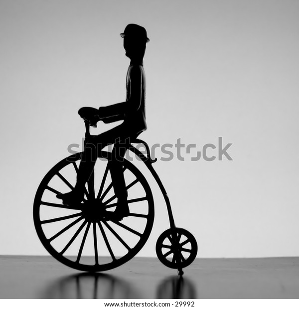 Silhouette of rider on old-fashioned bicycle