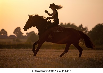 Silhouette of a riding cowgirl.