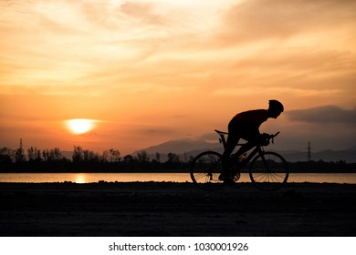 Silhouette a road bike cyclist man cycling in the morning.