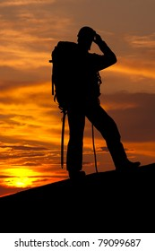silhouette of rock climber on sunset sky