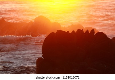 Silhouette of rock in ocean with sunset color background