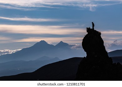 Silhouette of a rock peak with a person on the top, against the light, in front of the Ilinizas peaks at sunset