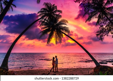 Silhouette of romantic affectionate couple kissing at sunset sea beach. Dating and relationship background with copyspace. Man and woman in love in honeymoon vacation.