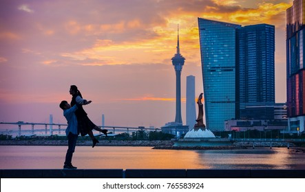 Silhouette romantic Asian couple with Kun Iam Statue and Macau Tower Convention in Macau, China, Asia. Man is carrying woman at seaside.