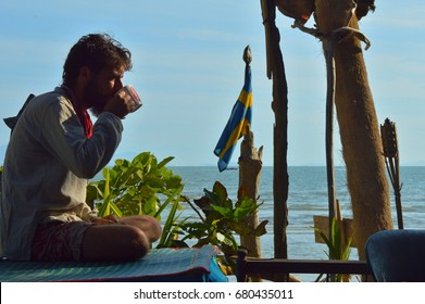 silhouette of romantic brown-haired boy with middle beard, big nose, neck-scarf drink coffee, meets dawn on the beach like in advertising. Hippie dude relaxation