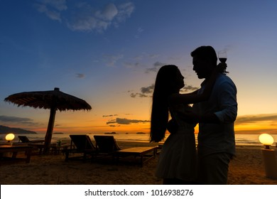 Silhouette of romantic couple enjoying a glass of wine with beautiful beach sunset. Valentine In Love concept