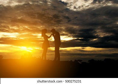 Silhouette Romantic couple in love ,man and women hold hands in nature ,sky with cloud in sunset time