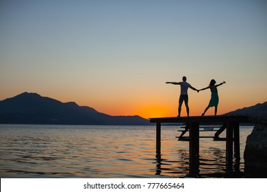 Silhouette Romantic couple lovers hug and kiss at colorful sunset on background.