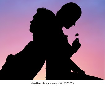 Silhouette of romantic couple sitting back to back on background of sunset