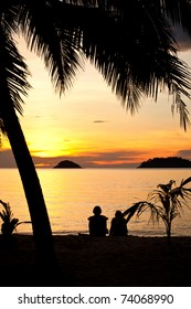Silhouette of a romantic couple sitting on a beach under palm trees at sunset. Sunlight is shimmering off of the water. Other islands can be seen at the distance.