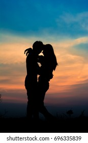 silhouette of romantic couple stand hugging on meadow at the sunset time . Have a beauty blue sky.