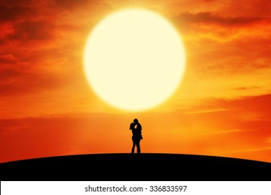 Silhouette of romantic couple standing on the hill and kissing at sunset time
