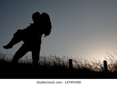 Silhouette of a romantic couple at sunset. He's holding her in his arms.