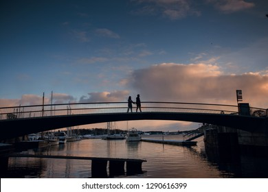 Silhouette of romantic couple walking holding hands on the bridge in the evening. Beautiful sky