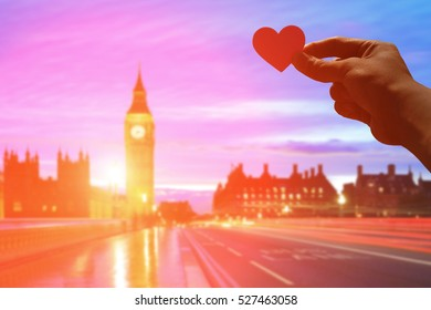 silhouette of romantic lovers hand hold love heart paper in Big Ben with sunset