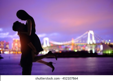 silhouette of romantic lovers with Odaiba in tokyo with sunset