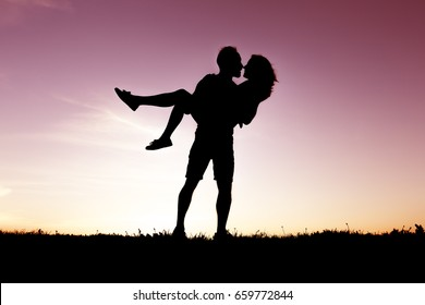 A silhouette of romantic lovers with sunset on the back