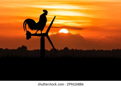 silhouette of roosters crow stand on a wind turbine. In the morning sunrise background