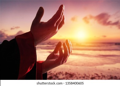 Silhouette rosary against cross in hand. Background sunrise