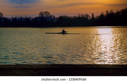 Silhouette of row boat against sunset on the lake