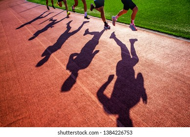 Silhouette of runners who race together in group on the athletics track. Track and Field photo