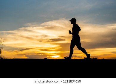 silhouette running alone at beautiful sunset in the park.