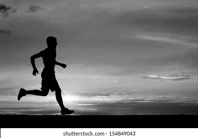 Silhouette of running man on sunset fiery background. Black and white. Element of design.