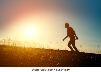 Silhouette of the running man at sunset background.