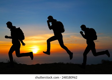 Silhouette of running men against the colorful sky. Silhouette of running man on sunset fiery background