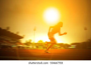 Silhouette of running race girl on the red track over the sun in the morning.