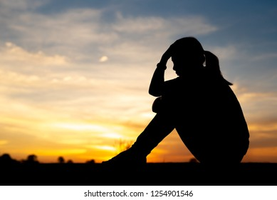 Silhouette of sad and depressed women sitting at walkway of park with sunset