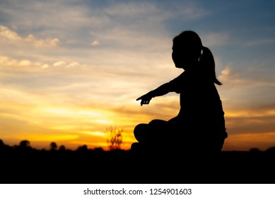 Silhouette of sad and depressed women sitting and pointing at walkway of park with sunset