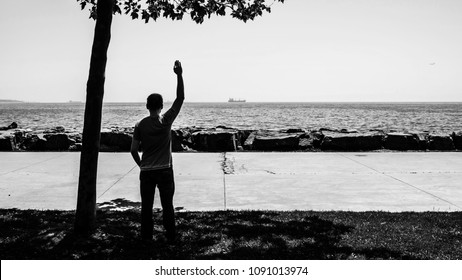 The silhouette of a sad man or boy standing alone on the seaside and waving her hand to the distant ship with feeling lonely. Time to go. Missing someone. Desire to go far away. Time to say goodbye.