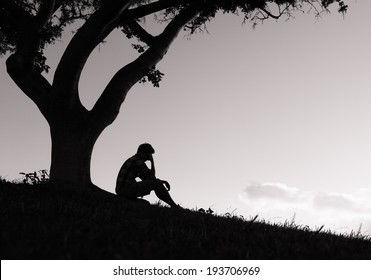 Silhouette of sad man sitting under the tree.