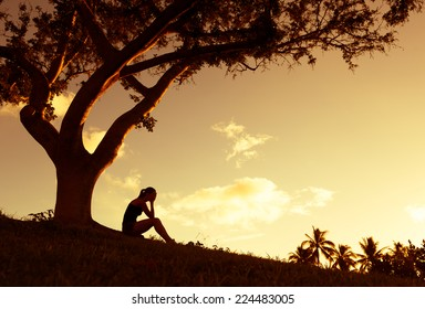 Silhouette of sad woman sitting under the tree