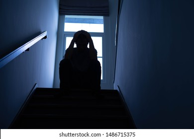Silhouette of a sad young man Sitting at the stairs in the dark, The sun is in sorrow, Life problems, illness.