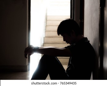 Silhouette of a sad young man sitting in the dark leaning against the wall with his back, The sun is in sorrow.