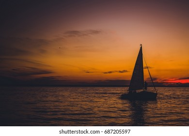 Silhouette of sailboat in the sea at sunset