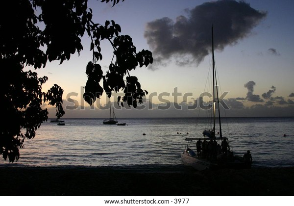 silhouette of sailboats at dusk