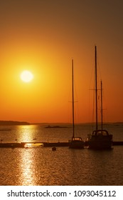 Silhouette of sailboats moored at an marina during a golden sunset in the swedish archipelago. Calm atmosphere