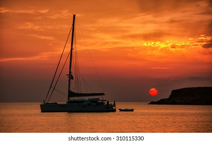 Silhouette of a sailing boat at sunset, in Syros island, Greece